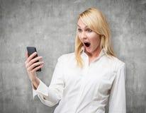 Mujer que mira el teléfono celular Fotografía de archivo libre de regalías