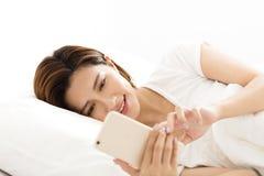 Mujer que mira el teléfono elegante en cama Fotos de archivo