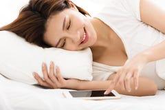 Mujer que mira el teléfono elegante en cama Fotos de archivo libres de regalías
