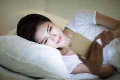 Mujer que mira el teléfono elegante en cama en la noche Fotos de archivo