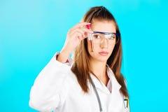 Mujer que mira el tubo químico Fotos de archivo libres de regalías
