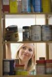 Mujer que mira en armarios de la cocina Fotos de archivo libres de regalías