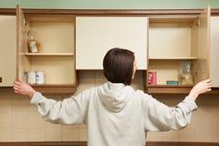 Mujer que mira en armarios vacíos de la comida imagen de archivo