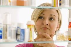 Mujer que mira en cabina de medicina Imágenes de archivo libres de regalías