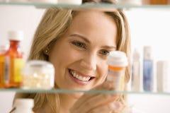 Mujer que mira en cabina de medicina Imagenes de archivo
