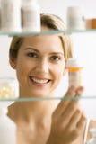 Mujer que mira en cabina de medicina Fotografía de archivo