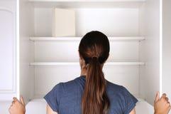 Mujer que mira en despensa vacía Foto de archivo libre de regalías