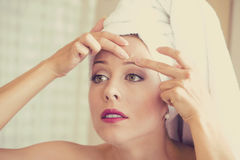 Mujer que mira en el espejo que exprime acné o espinilla en cara Imagen de archivo libre de regalías