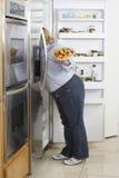 Mujer que mira en el refrigerador Imágenes de archivo libres de regalías