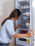 Mujer que mira en el refrigerador Fotos de archivo