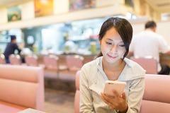 Mujer que mira en el teléfono móvil Fotos de archivo libres de regalías