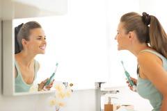Mujer que mira en espejo después de aplicar los dientes con brocha fotografía de archivo