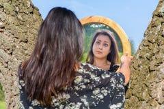 Mujer que mira en espejo entre los árboles Fotos de archivo