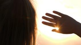 Mujer que mira en la distancia que oculta del sol