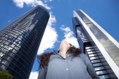 Mujer que mira en la parte superior rascacielos Foto de archivo
