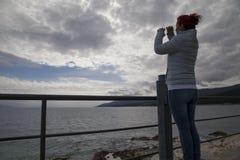 Mujer que mira en los prismáticos imaginarios Imagen de archivo libre de regalías