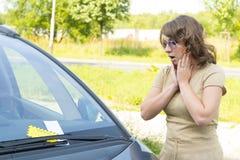 Mujer que mira en multa de aparcamiento Imágenes de archivo libres de regalías