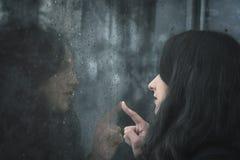 Mujer que mira en ventana lluviosa imágenes de archivo libres de regalías