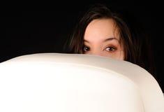 Mujer que mira a escondidas de detrás una butaca blanca Fotografía de archivo