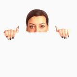 Mujer que mira a escondidas detrás de un whiteboard Foto de archivo