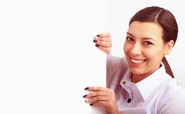 Mujer que mira a escondidas detrás de un whiteboard Fotografía de archivo
