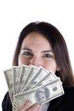 Mujer que mira a escondidas sobre cientos cuentas de dólar. Fotografía de archivo libre de regalías