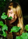 Mujer que mira a escondidas a través de las hojas fotos de archivo libres de regalías