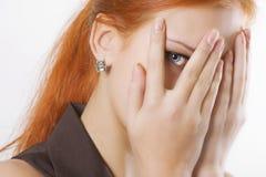 Mujer que mira a escondidas a través de los dedos Fotos de archivo