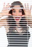 Mujer que mira a escondidas a través de persianas Imágenes de archivo libres de regalías