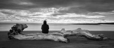 Mujer que mira fijamente hacia fuera al mar y a un horizonte brillante fotos de archivo