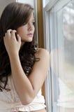 Mujer que mira fijamente la ventana Fotos de archivo
