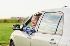 Mujer que mira fuera de la ventanilla del coche y que lleva a cabo una llave Foto de archivo