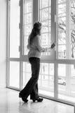 Mujer que mira fuera de una ventana Fotos de archivo