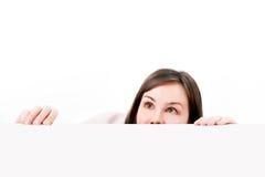 Mujer que mira furtivamente sobre el fondo blanco. Fotos de archivo libres de regalías