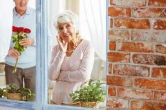 Mujer que mira furtivamente a través de la ventana foto de archivo libre de regalías