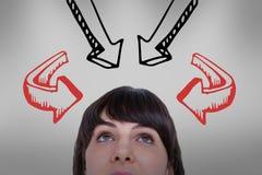 Mujer que mira hacia arriba con las flechas sobre sus cabezas Imagen de archivo libre de regalías