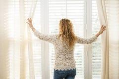 Mujer que mira hacia fuera la ventana Foto de archivo libre de regalías