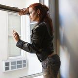 Mujer que mira hacia fuera la ventana. Imagen de archivo