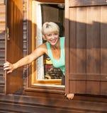Mujer que mira hacia fuera la ventana de una cabaña Fotografía de archivo libre de regalías