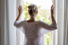 Mujer que mira hacia fuera la ventana en pijama fotos de archivo libres de regalías