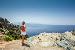 Mujer que mira hacia fuera sobre costa mediterránea de Cap Corse en corazón Foto de archivo