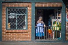 Mujer andina que mira hacia fuera su pequeña tienda Fotos de archivo libres de regalías