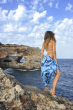Mujer que mira horizonte del océano en el acantilado de la roca por la orilla de mar en abrigo de la playa de los sarong Fotografía de archivo libre de regalías
