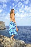 Mujer que mira horizonte del océano en el acantilado de la roca por la orilla de mar en abrigo de la playa de los sarong Imagenes de archivo