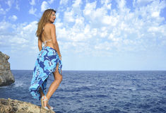 Mujer que mira horizonte del océano en el acantilado de la roca por la orilla de mar en abrigo de la playa de los sarong Imagen de archivo libre de regalías