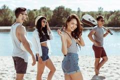 Mujer que mira la cámara mientras que camina con los amigos en la playa Imágenes de archivo libres de regalías