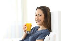 Mujer que mira la cámara que sostiene el zumo de naranja foto de archivo
