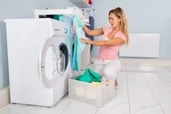 Mujer que mira la camiseta azul después de lavar planchar foto de archivo libre de regalías