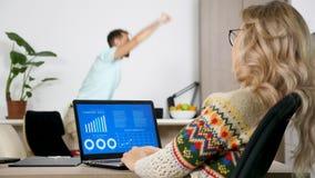 Mujer que mira la carta financiera animada en el ordenador en la sala de estar almacen de video