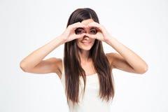 Mujer que mira la cámara a través de sus fingeres Fotos de archivo libres de regalías
